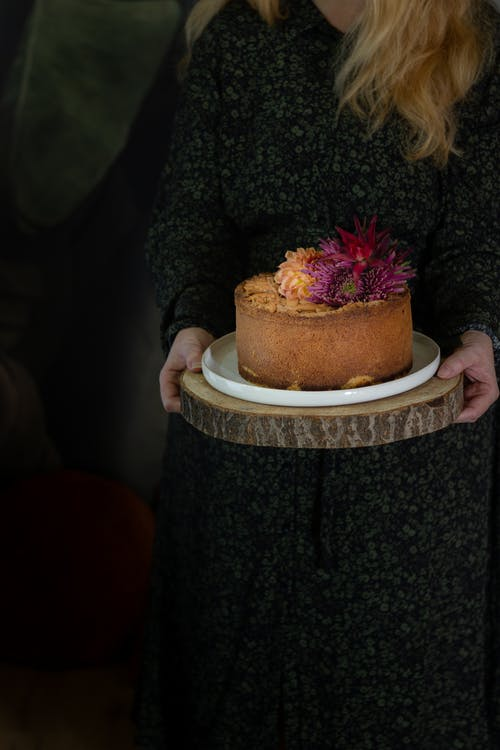 Woman Holding a Cake on a Wooden Tray