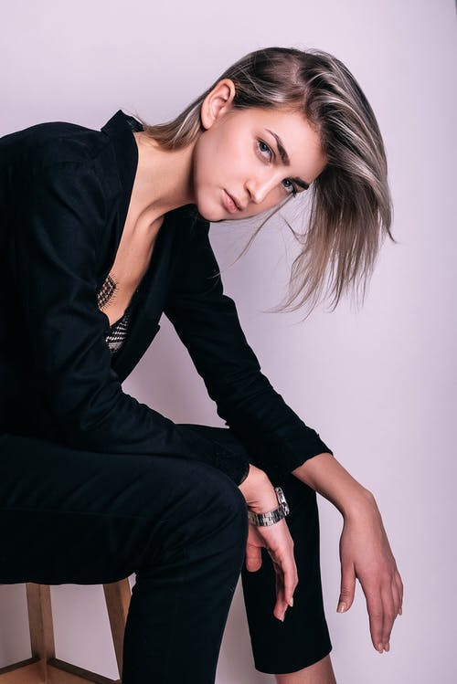 Side view of young attentive female in trendy wear and wristwatch leaning forward on stool while looking at camera