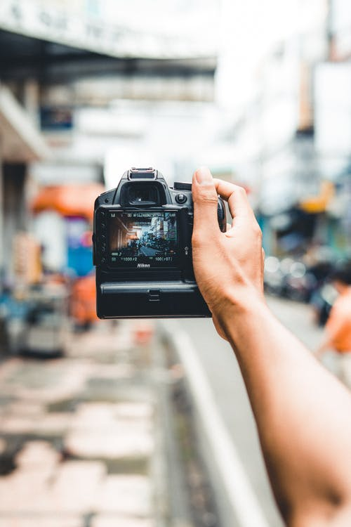 Crop unrecognizable person taking photo of street on professional camera