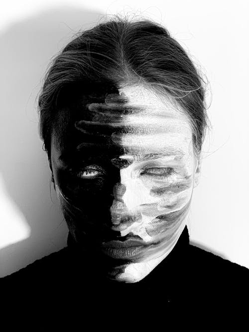 Black and white of spooky weird female wearing pullover with paints on face rolling eyes while standing on white background