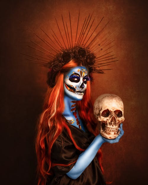 Unrecognizable young female with floral headband in long red hair and La Calavera Catrina makeup holding artificial skull and looking at camera during Mexican Dia de Muertos party