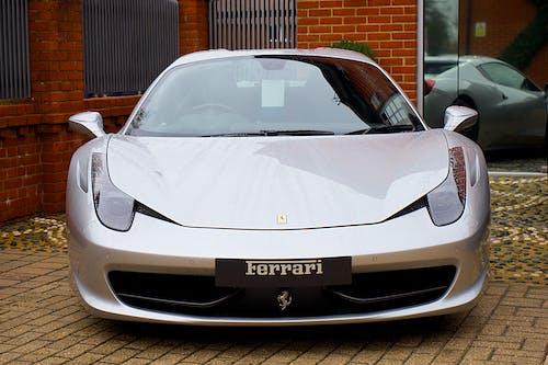 Grey Ferrari Parked Near Brick Wall