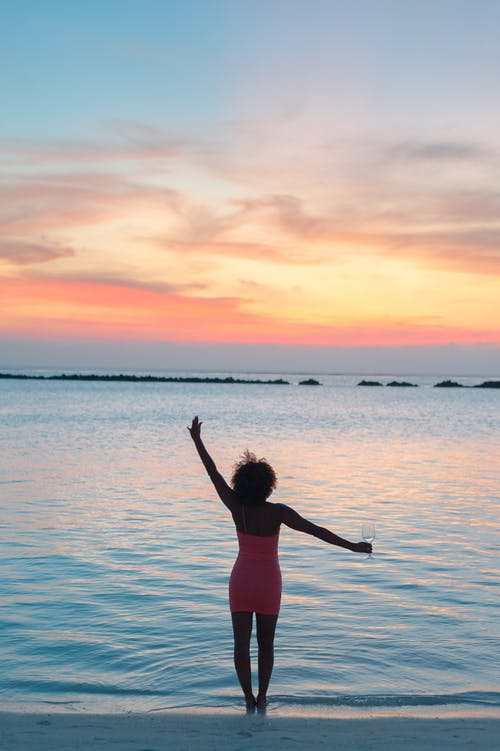 Woman in Red Bikini Standing on Water during Sunset