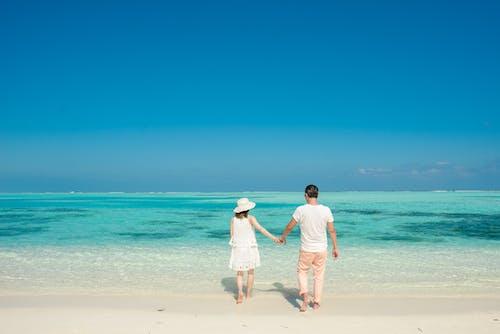 Man and Woman Walking on Beach