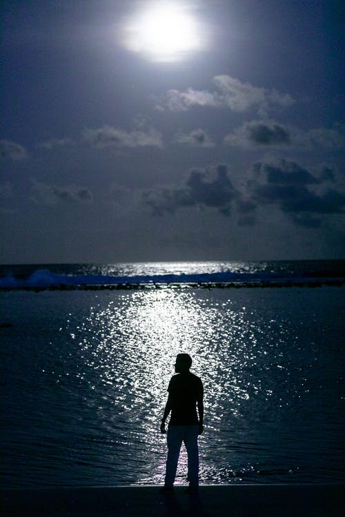 Man in Black Jacket Standing on Seashore during Night Time