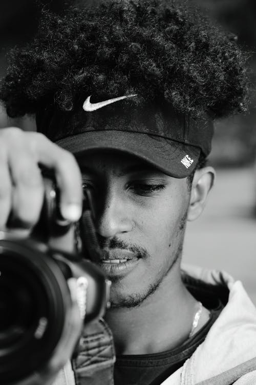 Man in Black Nike Fitted Cap Holding Black Camera