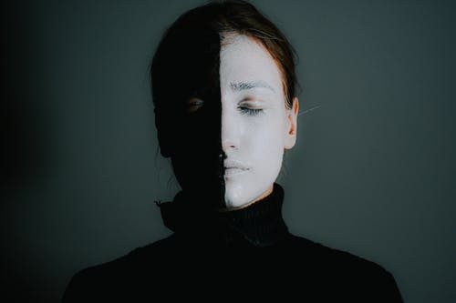 Female with face painted in black and white standing with closed eyes