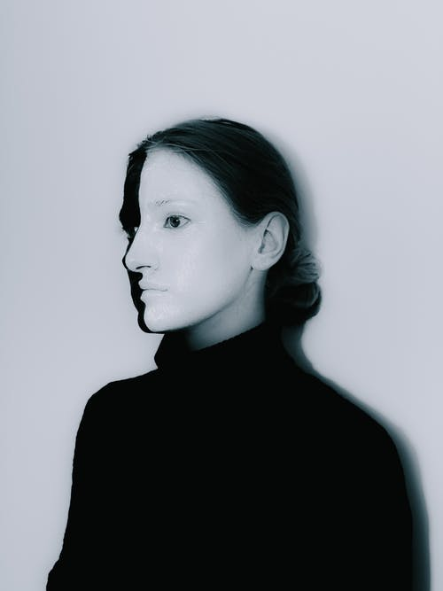 Black and white of serious female with face painted half in white and half in black in sweater standing against white background