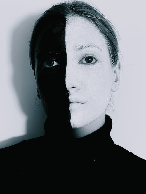 Emotionless woman with face in black and white paints against white wall
