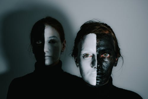 Unemotional models with face painted in white and black paints standing in room with light wall and looking at camera