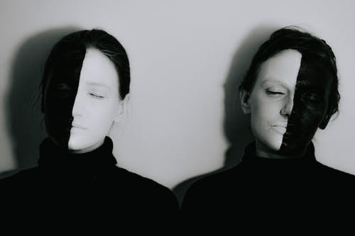 Black and white of women with face painted in contrast black and white colors standing with closed eyes against white background