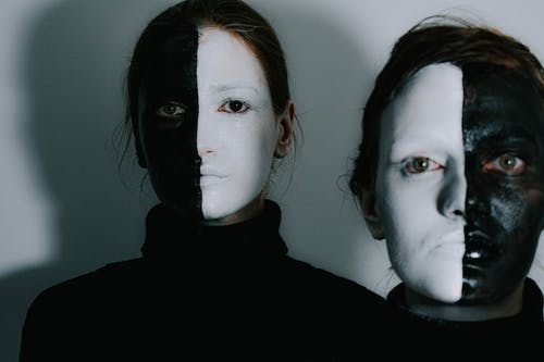 Emotionless women with face covered with black and white paints