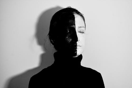 Black and white of woman with face painted in white and black colors standing with closed eyes against light wall with shadow