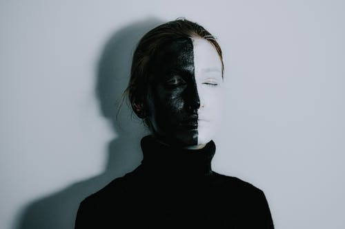 Mysterious female with face painted half in white and half in black colors standing with closed eyes against light background