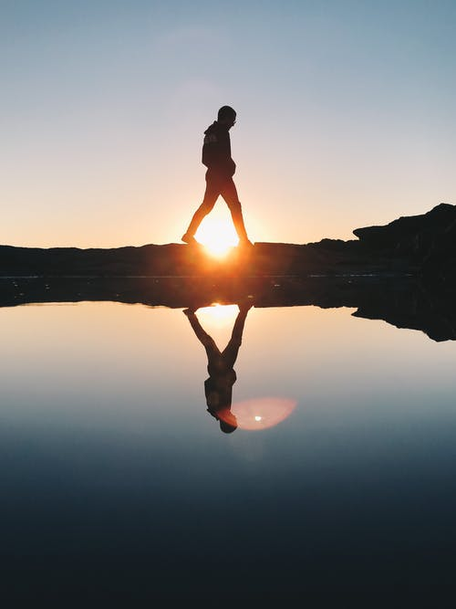 Silhouette of Man Standing on Rock Formation Near Body of Water during Sunset