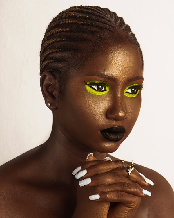 Beautiful young black woman with golden shimmering makeup looking away