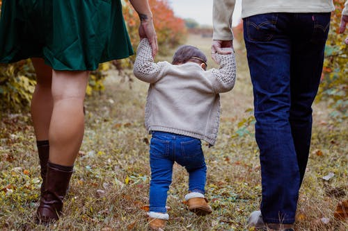 Crop parents with toddler strolling in nature