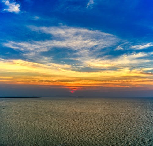 Picturesque view of wavy ocean with horizon under colorful sky with clouds at sunset