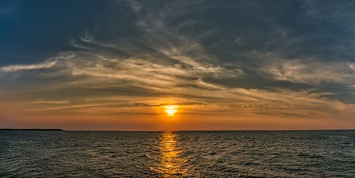 Scenery view of endless rippled ocean with horizon under glowing sun in bright sky at sundown