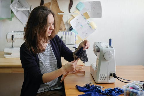 Concentrated dressmaker measuring piece of fabric with tape before sewing on machine at table in workshop