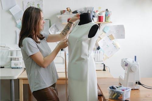 Positive seamstress measuring dress on dummy