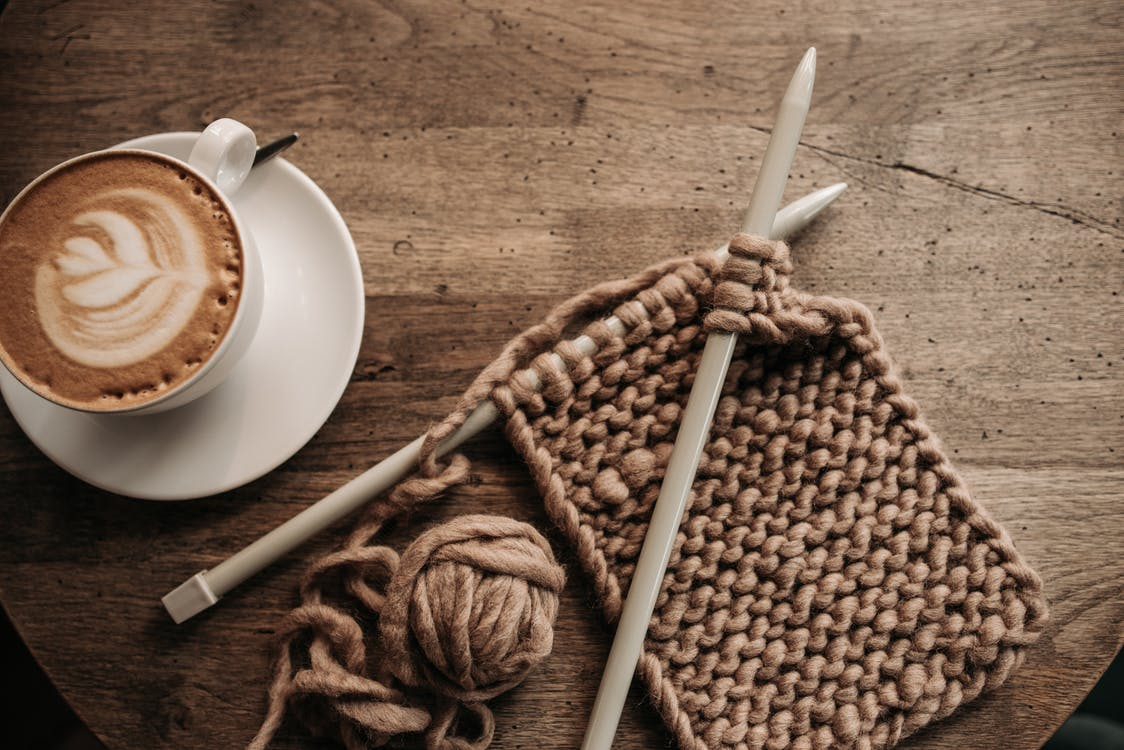 White Ceramic Mug With Coffee Beside Brown and Black Rope on Brown Wooden Table