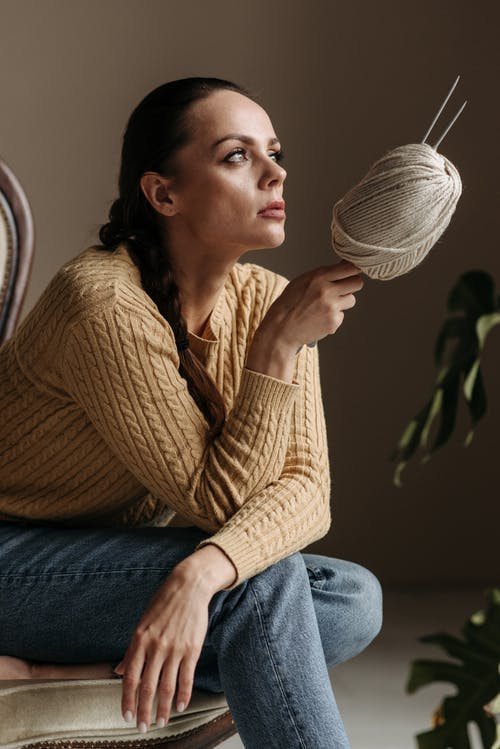 Woman in Brown Sweater and Blue Denim Jeans Sitting on Chair