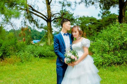 Man in Blue Suit Jacket Beside Woman in White Dress