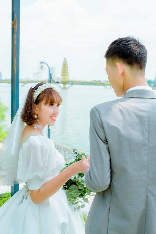 Man in Gray Suit Jacket Holding Hands with Woman in White Wedding Dress