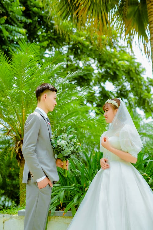 Man and Woman in Wedding Dress Standing Under Green Tree