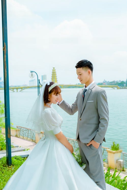 Man in Gray Suit Jacket and Woman in White Dress