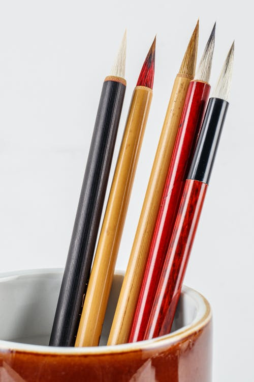 Assorted colorful Japanese calligraphy brush pens with spiky tips and bamboo shafts on white background