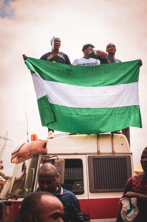 People in White Van Holding Green and White Flag