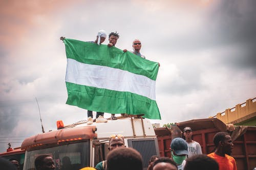 Man in Green Shirt Holding Green Flag