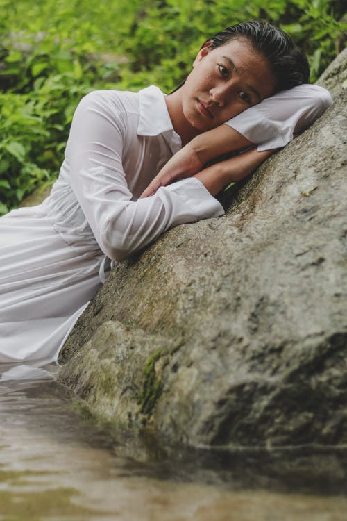Romantic young ethnic female leaning on rocky boulder after swimming in pond