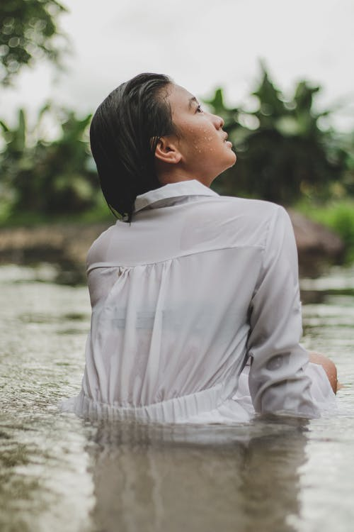 Back view of pensive young Asian lady in white dress standing in calm lake water and looking up during summer holidays in tropical resort