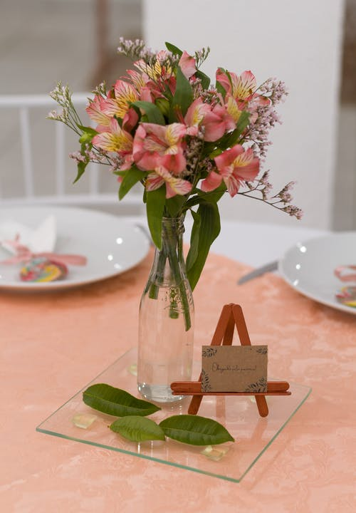 Pink and Purple Flowers in Clear Glass Vase on Brown Wooden Table