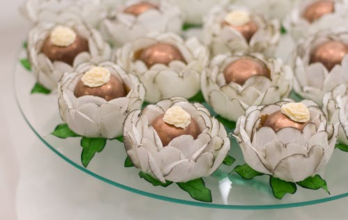 White and Brown Flower Petals on Green Ceramic Bowl