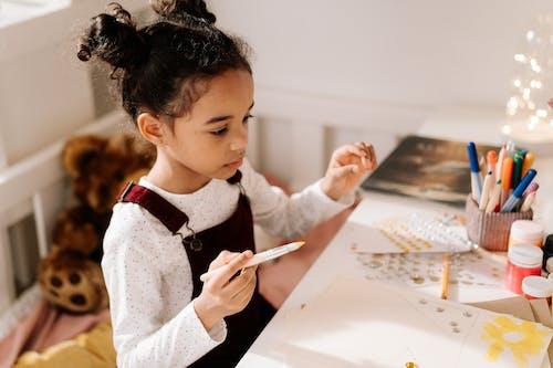 Girl in White Sweater Doing an Artwork