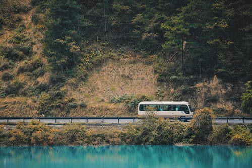 White and Black Bus on Bridge over River