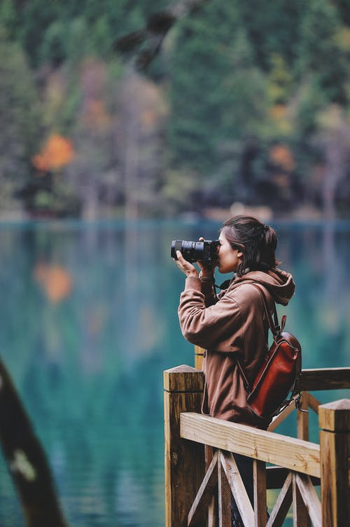 Man in Brown Jacket Taking Photo of Body of Water