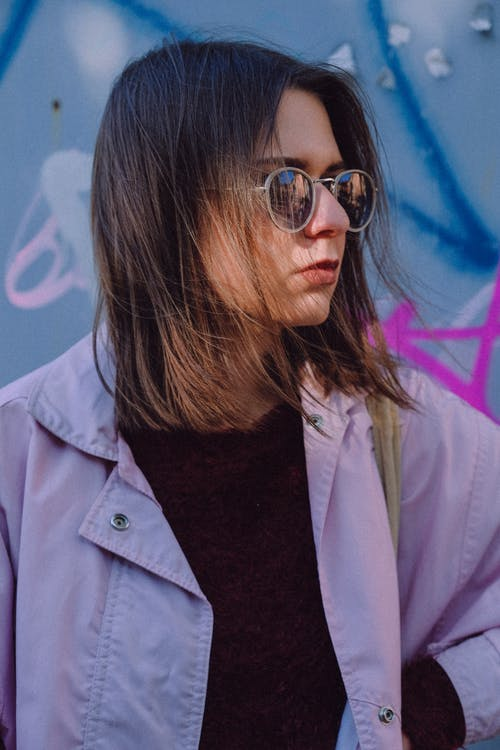 Confident brunette female with messy hair wearing trendy sunglasses against colorful wall looking away
