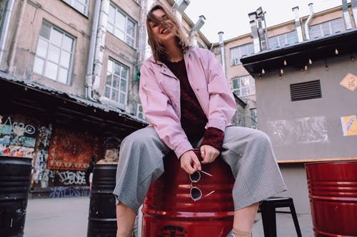 Low angle of stylish positive female wearing casual clothes smiling brightly while sitting on metal barrel