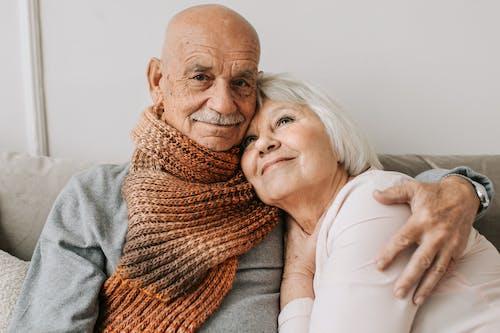 Man in Gray Sweater Hugging Woman in White Shirt