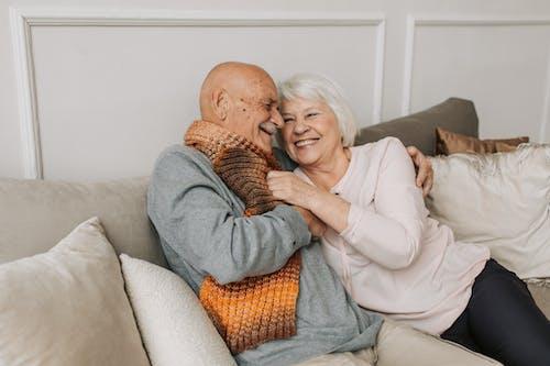 Man in Gray Sweater Hugging Woman Beside Him