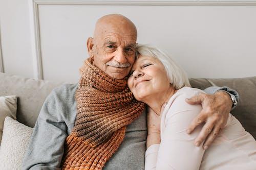 Man in Gray Sweater Hugging Woman