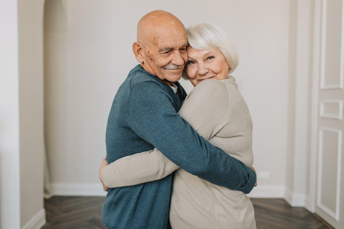 Man in Gray Sweater Hugging Woman in Blue Sweater