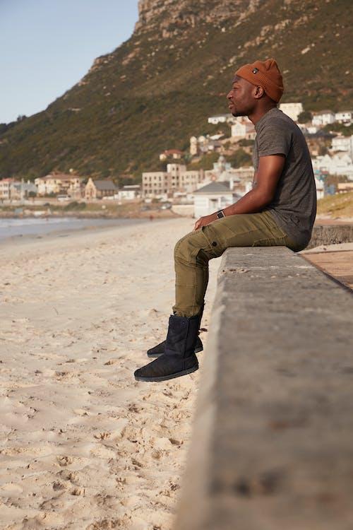 Black man sitting on stone fence