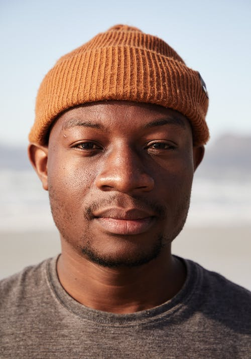 Calm masculine black man in knitted hat