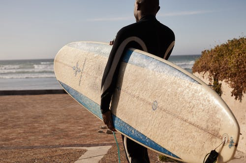 Unrecognizable black surfer carrying surfboard on sea shore
